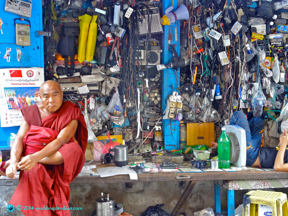 Maroon-robed Buddhist monk sitting amid chaotic old-tech market stall in central bazaar, Rangoon, Myanmar
