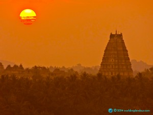 Dreamlike, visionary image of orange sunset over temples and palm jungle; Virupaksha temple, Hampi, Karnataka, India